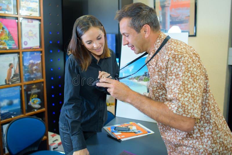 Hombre que muestra las broches del día de fiesta del agente de viajes fotografía de archivo libre de regalías