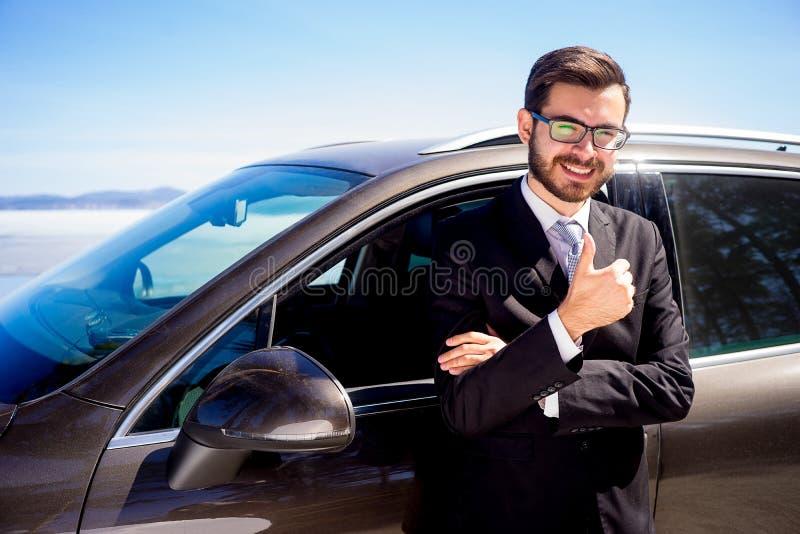 Hombre que muestra los pulgares para arriba cerca de un coche imagenes de archivo