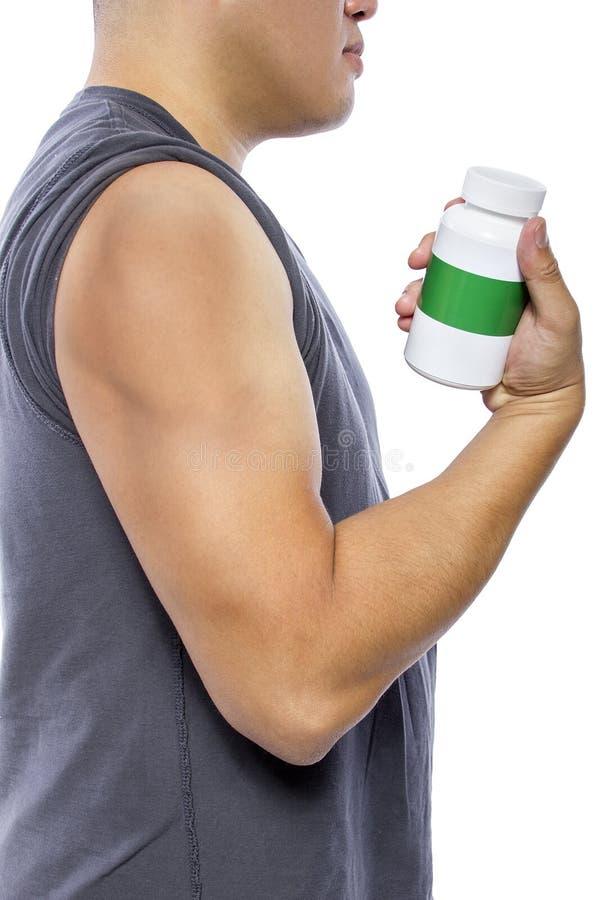 Hombre que muestra resultados del bíceps de usar suplementos foto de archivo libre de regalías
