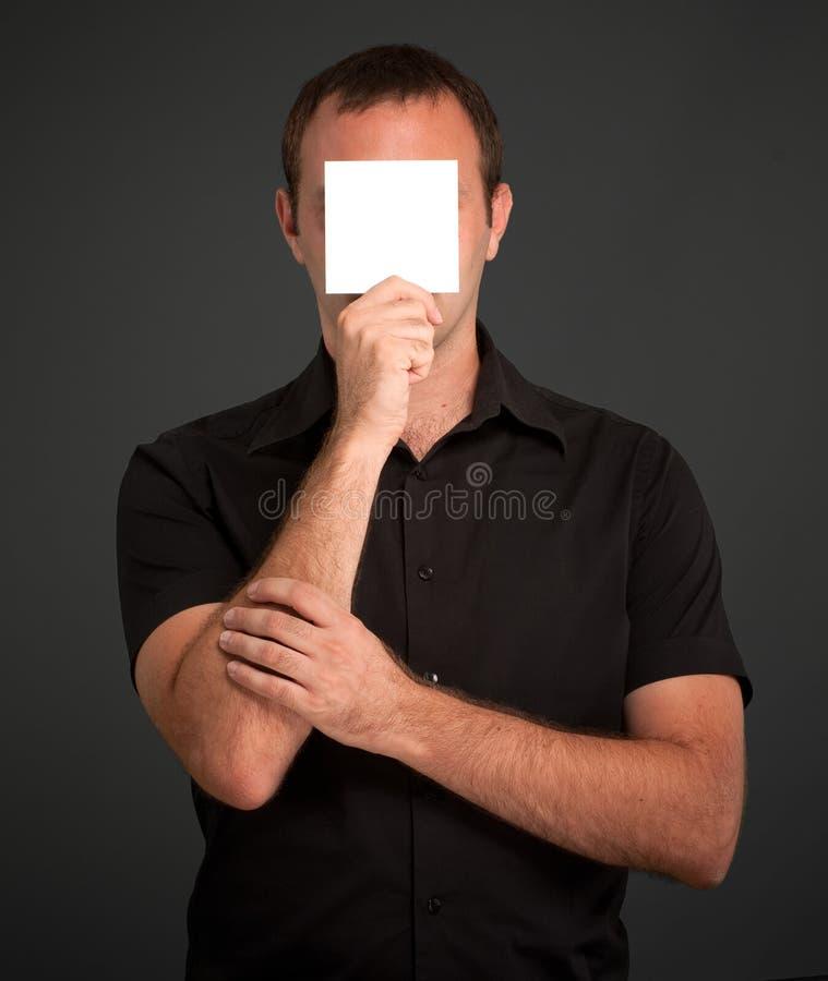 Hombre que oculta detrás de una nota en blanco