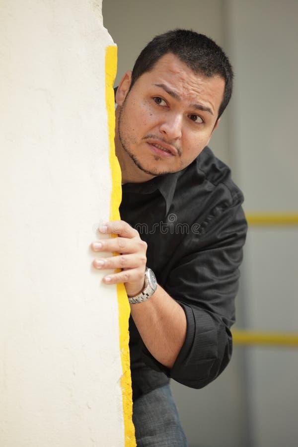 Hombre que oculta detrás de una pared