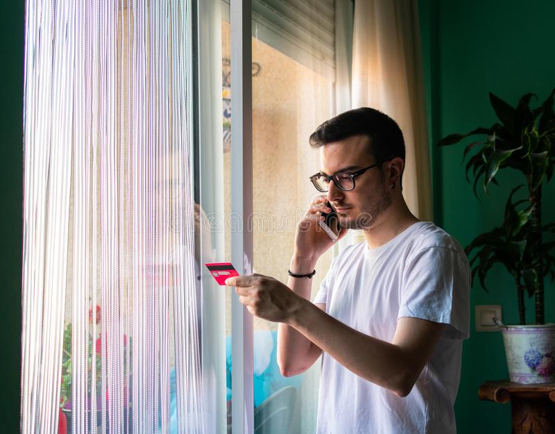 Hombre que paga con una tarjeta de crédito con el móvil cerca de la ventana imagenes de archivo