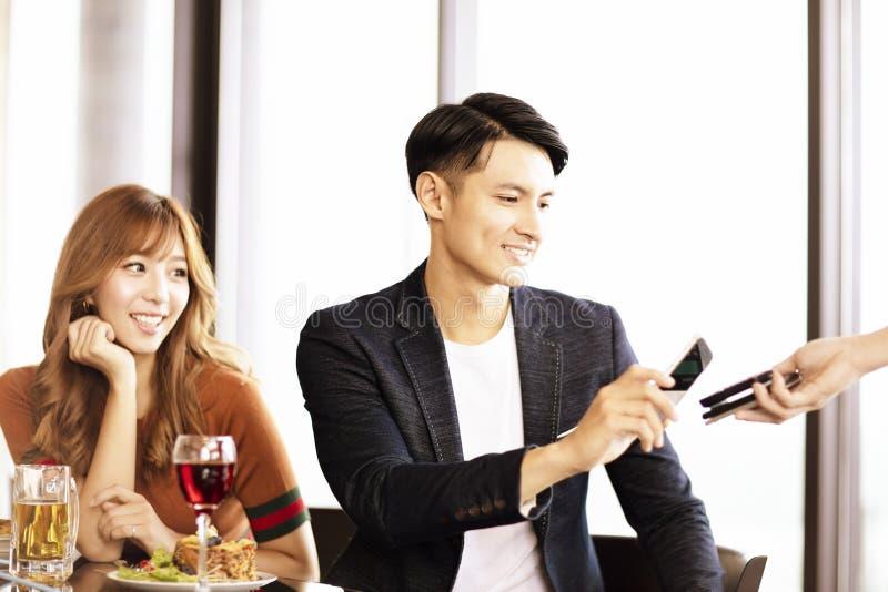hombre que paga por el teléfono elegante en restaurante foto de archivo