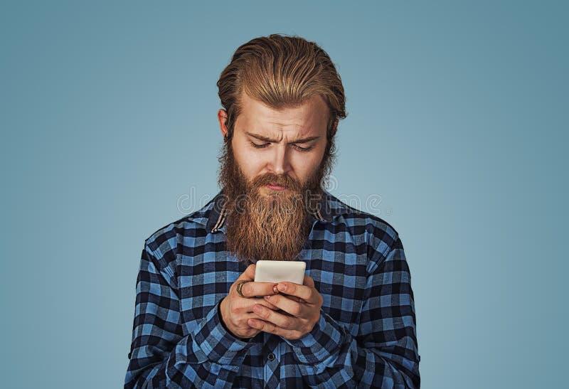 Hombre que parece perplejo y escéptico mientras que usando el teléfono móvil fotos de archivo libres de regalías