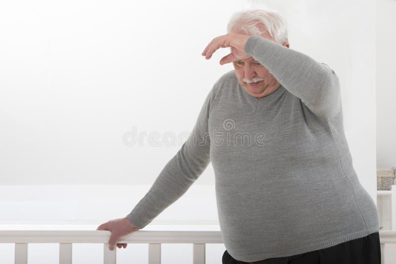 Hombre que parece preocupado con la mano en la frente imagen de archivo