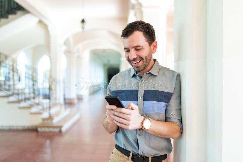 Hombre que pasa el cotilleo del tiempo en Smartphone mientras que se inclina en Colum foto de archivo libre de regalías
