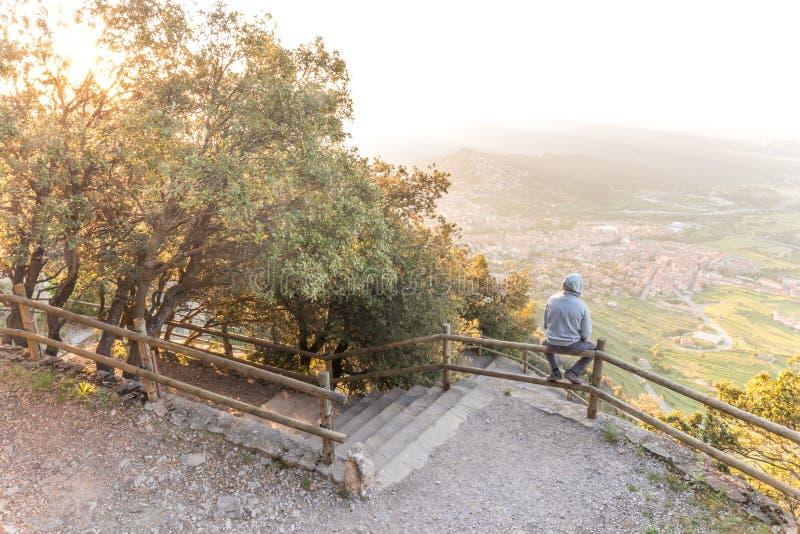 Hombre que pasa por alto paisaje hermoso en el banco de la montaña fotos de archivo