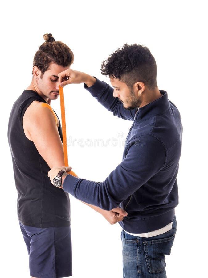 Hombre que pega las cintas de Kinesio en los brazos del deportista imagen de archivo