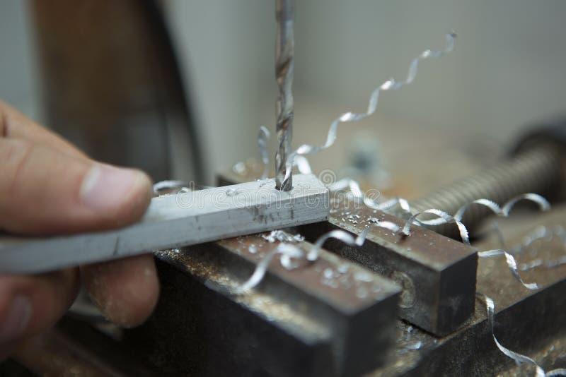 Hombre que perfora adentro la placa de acero con el taladro del banco Primer eléctrico fotos de archivo