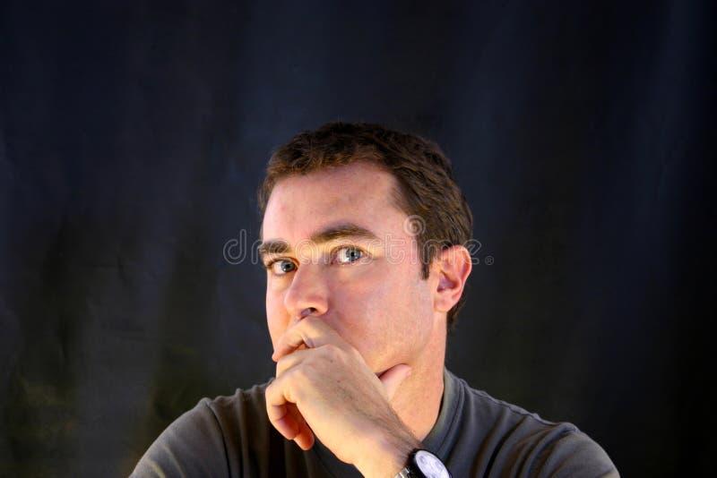 Hombre que piensa con el fondo negro imagen de archivo