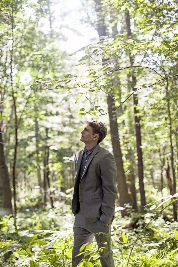 Hombre que piensa en bosque fotografía de archivo