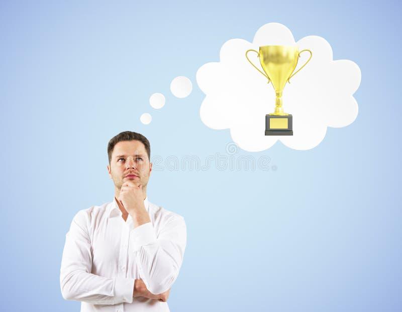 Hombre que piensa en el trofeo imagen de archivo libre de regalías