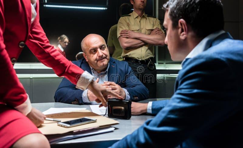 Hombre que piensa en su declaración y el cargo criminal durante la interrogación imagen de archivo libre de regalías