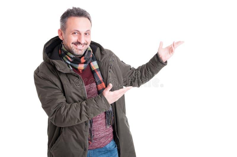 Hombre que plantea el invierno que lleva que muestra algo imagen de archivo