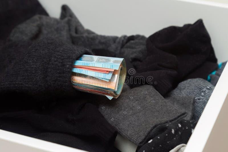 Hombre que pone, dinero de ocultación en sus calcetines para ahorrarlo No mostrar ninguna confianza en instituciones financieras  fotos de archivo