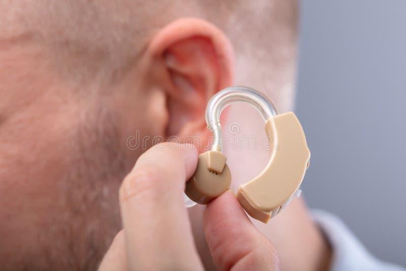 Hombre que pone el aud?fono en su o?do fotos de archivo