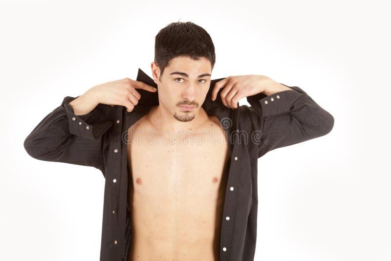Hombre que pone en la camisa foto de archivo libre de regalías
