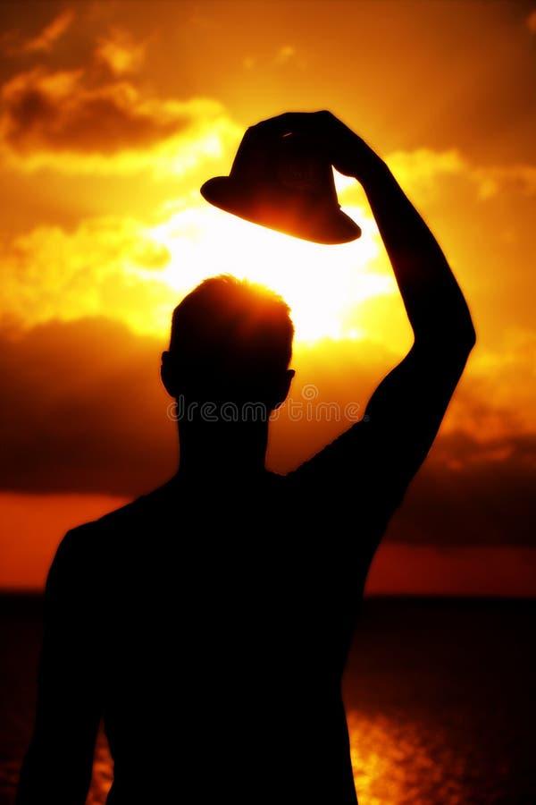 Hombre que pone en su sombrero en puesta del sol imágenes de archivo libres de regalías