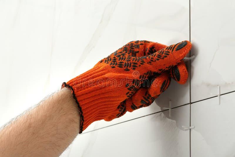Hombre que pone la cruz plástica en junta entre las baldosas cerámicas en la pared Trabajos del edificio y de renovaci?n imagen de archivo