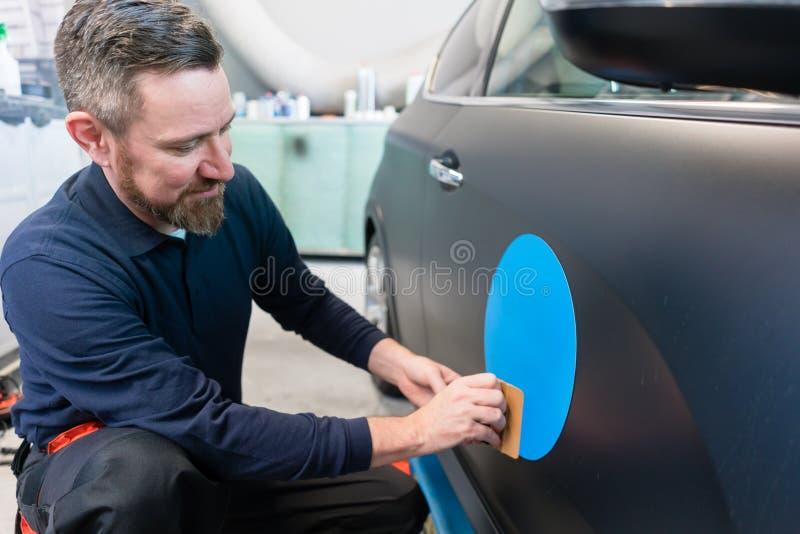 Hombre que pone la etiqueta engomada con lema de la compañía en un coche fotografía de archivo libre de regalías