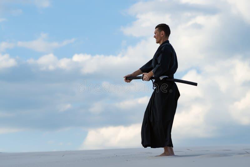 Hombre que practica arte marcial japonés en desret foto de archivo