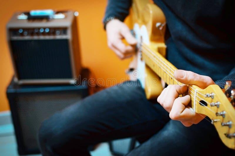 Hombre que practica la guitarra eléctrica que juega con los amplificadores Lección de la guitarra fotografía de archivo libre de regalías