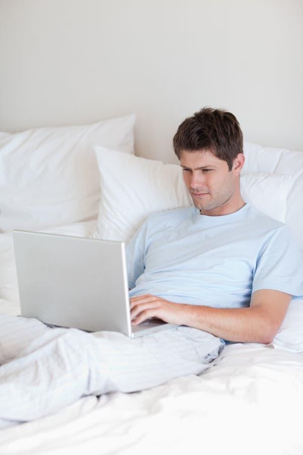 Hombre que practica surf el Internet en cama fotografía de archivo libre de regalías