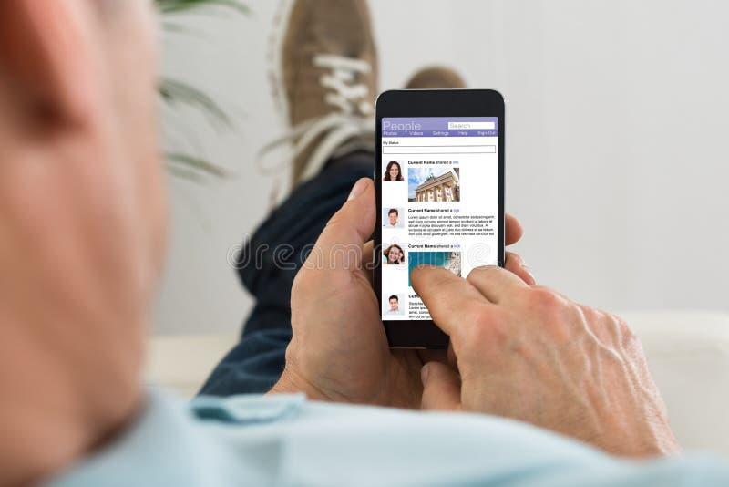 Hombre que practica surf en sitio social del establecimiento de una red usando el teléfono móvil imagen de archivo