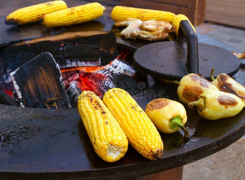 Hombre que prepara la barbacoa al aire libre El cocinar de la carne de vaca, del pollo, del maíz y de las verduras asados a la pa foto de archivo