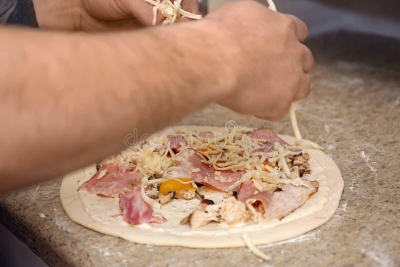 Hombre que prepara la pizza en la tabla Receta del horno foto de archivo