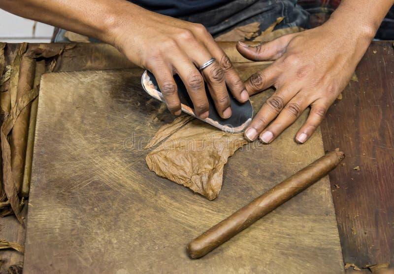 Hombre que prepara los cigarros cubanos imagenes de archivo