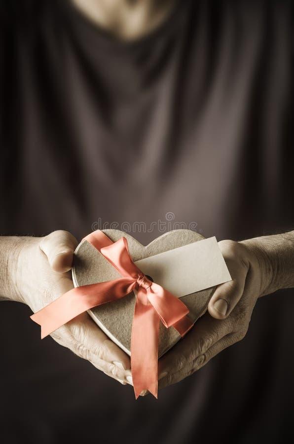 Hombre que presenta el regalo de la caja del corazón fotografía de archivo libre de regalías