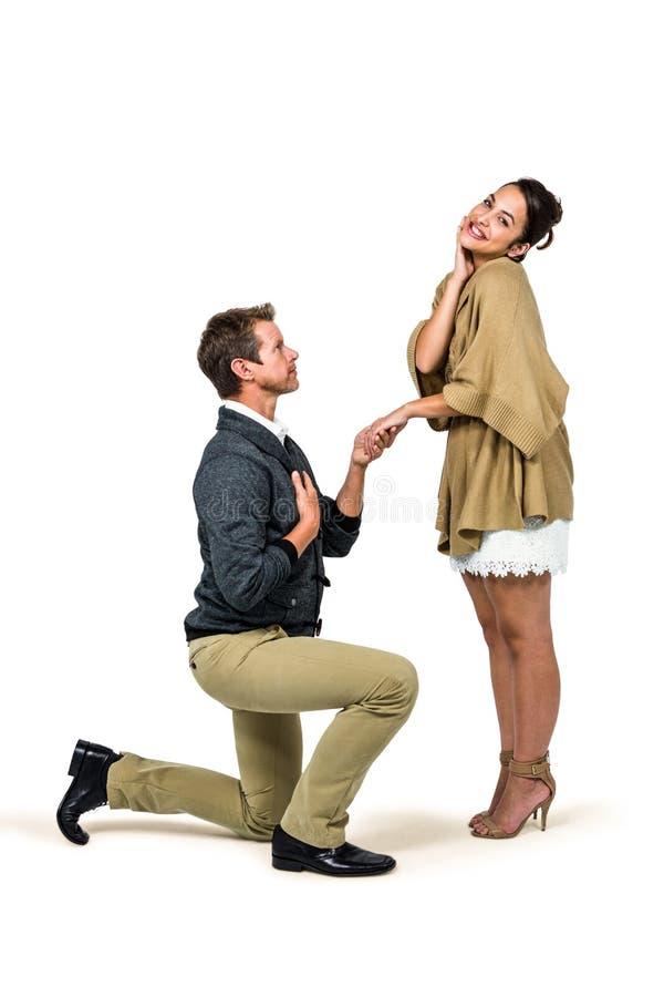 Hombre que propone a la mujer mientras que se arrodilla foto de archivo libre de regalías