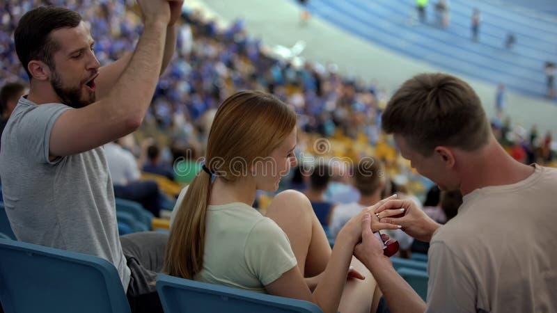 Hombre que propone matrimonio a la muchacha en el estadio, anillo de compromiso que lleva, romántico fotografía de archivo