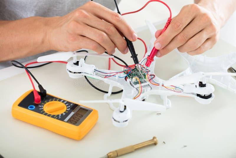 Hombre que prueba la corriente eléctrica del abejón usando la herramienta del multímetro fotos de archivo
