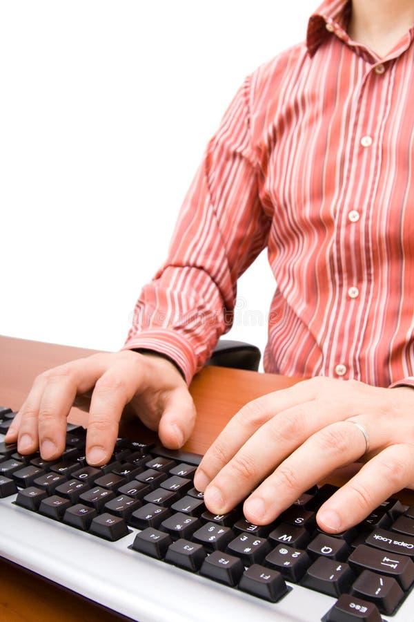 Hombre que pulsa en el teclado de ordenador fotos de archivo libres de regalías