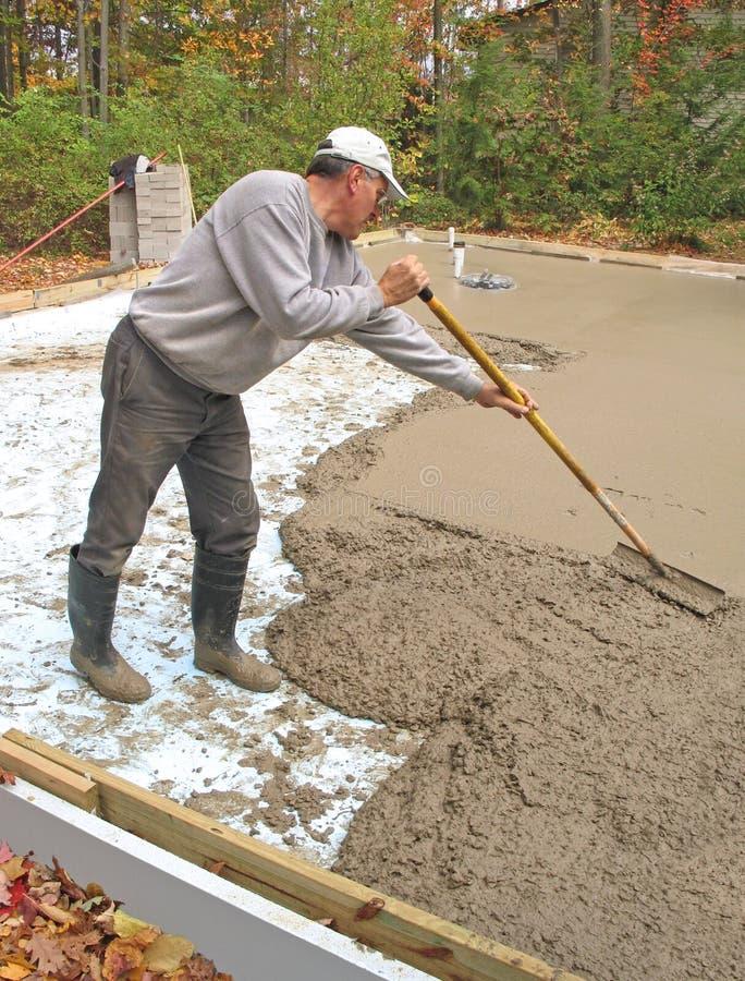 Hombre que rastrilla el concreto foto de archivo