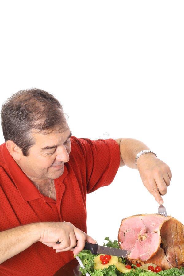 Hombre que rebana una vertical del jamón imagen de archivo