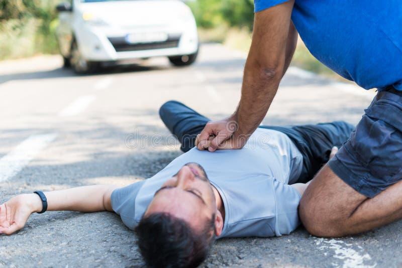 Hombre que recibe los primeros auxilios después de un accidente de tráfico imagen de archivo libre de regalías