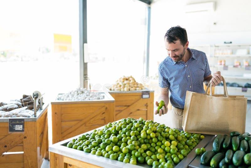Hombre que recoge los limones saludables del mercado vegetal foto de archivo libre de regalías