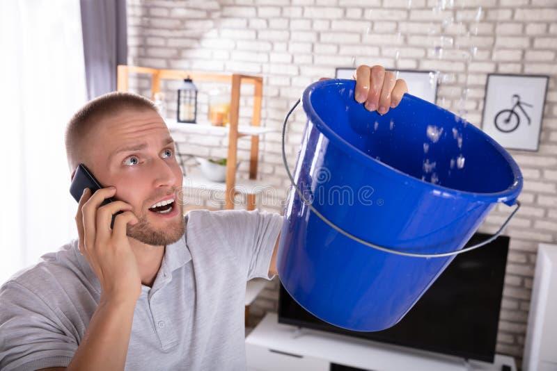 Hombre que recoge salida del agua en cubo mientras que llama al fontanero fotos de archivo