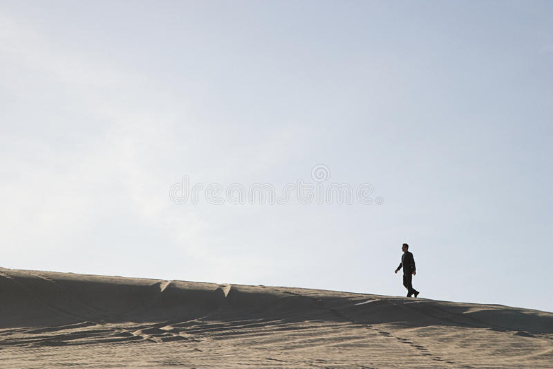 Hombre que recorre en desierto foto de archivo