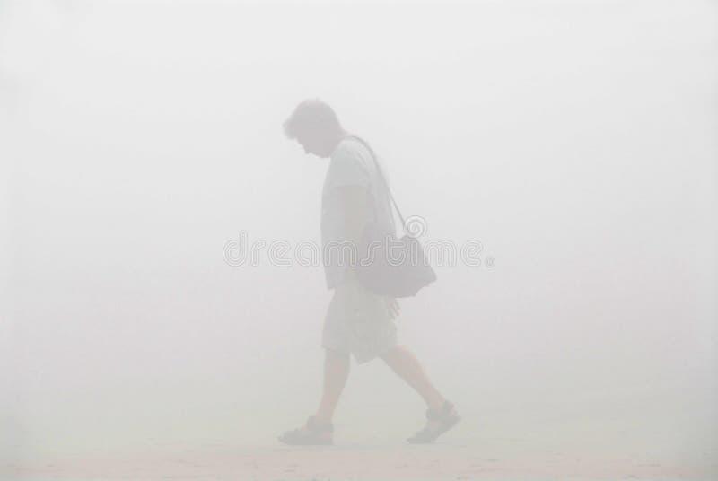 Hombre que recorre en una niebla imagenes de archivo
