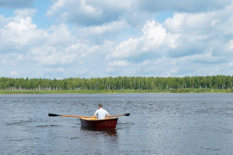 Hombre que rema en un barco de madera, flotando en un lago en un día soleado, fin de semana activo, vista posterior imagen de archivo libre de regalías