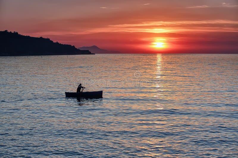 Hombre que rema un barco durante puesta del sol foto de archivo libre de regalías
