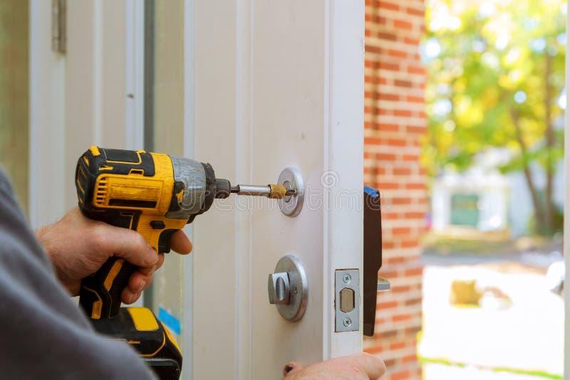 hombre que repara el tirador primer del worker& x27; manos de s que instalan el nuevo armario de la puerta fotos de archivo libres de regalías