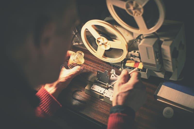 Hombre que repara la cinta video quebrada de 8m m con pegamento imagenes de archivo