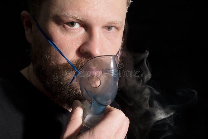Hombre que respira a través de máscara del nebulizador imagen de archivo