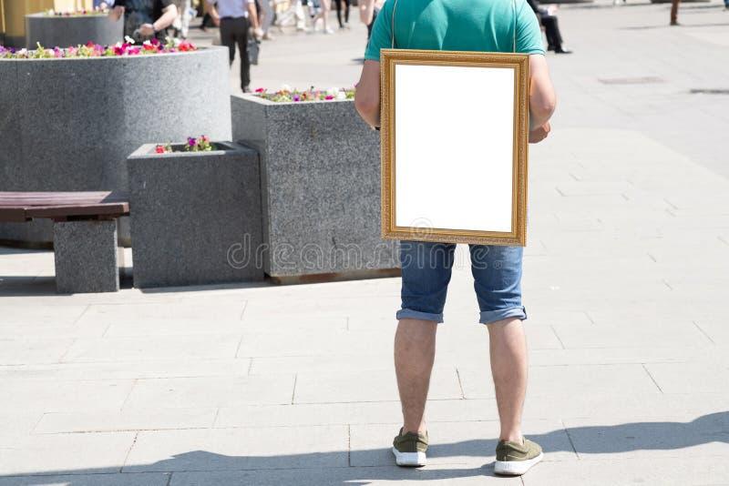 hombre que retiene a un tablero blanco en blanco en el suyo fotografía de archivo