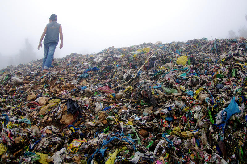 Hombre que revisa una montaña de la basura imagen de archivo libre de regalías